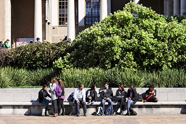 students sitting on the bottom step outside the Library in front of Sarah Baartman Hall