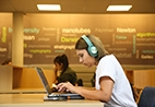 Student seated with headphones on works on laptop inside the library