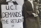 "A woman holds a placard saying ""UCT demands the return of academic freedom"" beside a woman holding a lit torch. They are both wearing academic dress."